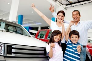 Happy family at a car dealership with arms up celebrating having a new car