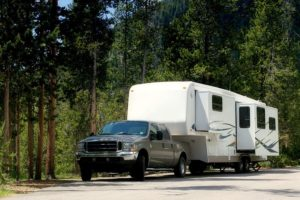 A pickup truck hitched to a large RV camper trailer in a wooded park